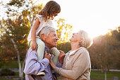 Grandparents Giving Granddaughter A Shoulder Ride In Park