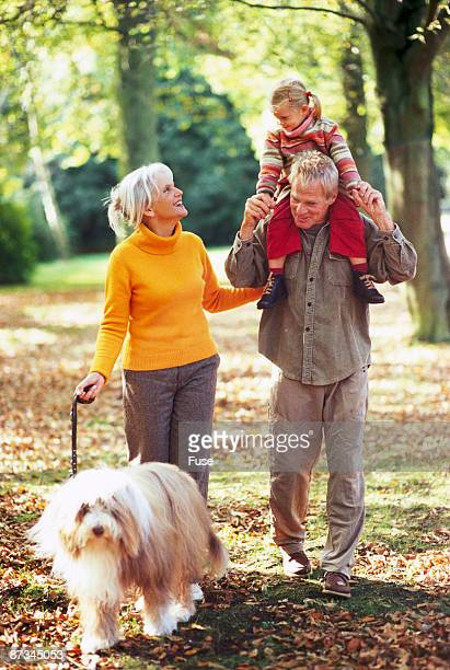 Grandparents going for a walk with granddaughter and dog