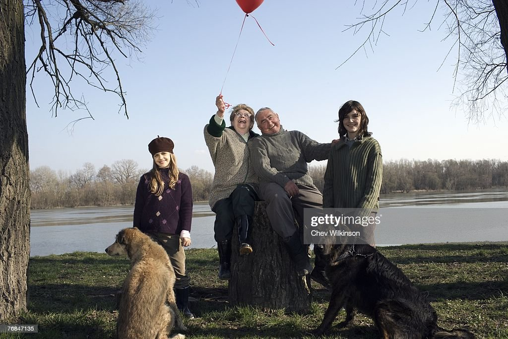 Grandparents, grandson (12-14) and granddaughter (10-12) with two dogs by river : Stock Photo