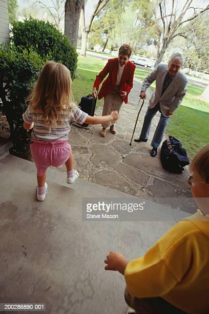 Grandparents greeting grandchildren (3-4), elevated view