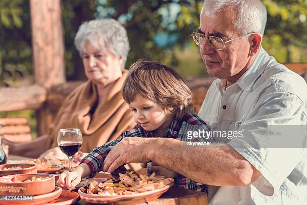 Grandparents having lunch with their grandson in a restaurant.