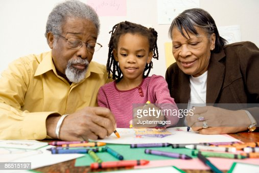 Grandparents helping girl with homework : Stock Photo