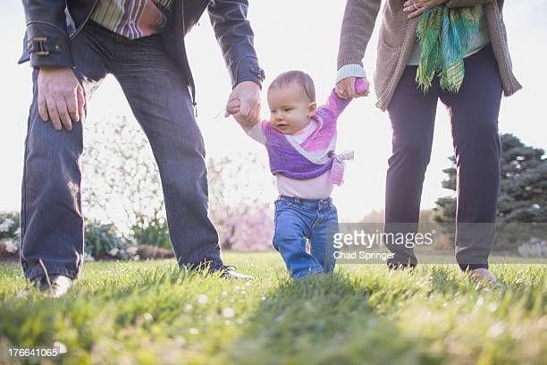 Grandparents holding granddaughter hands in park
