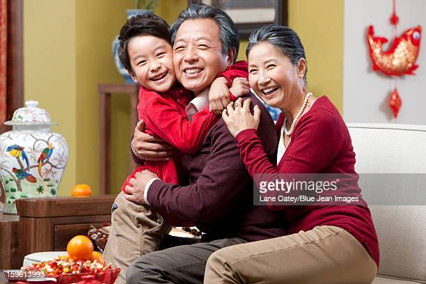 Grandparents hugging grandson during Chinese New Year