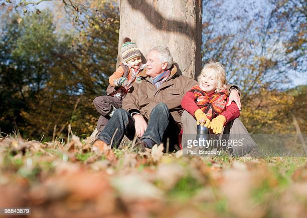 Grandparents leaning against tree with grandson
