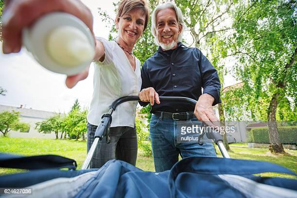 Abuelos Observando a sus nietos en cochecito para niños,