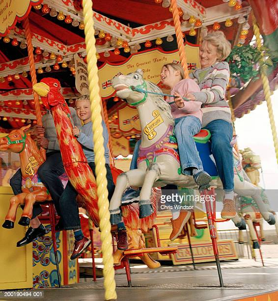 Grandparents on carousel with granddaughter (7-9) and grandson (7-9)