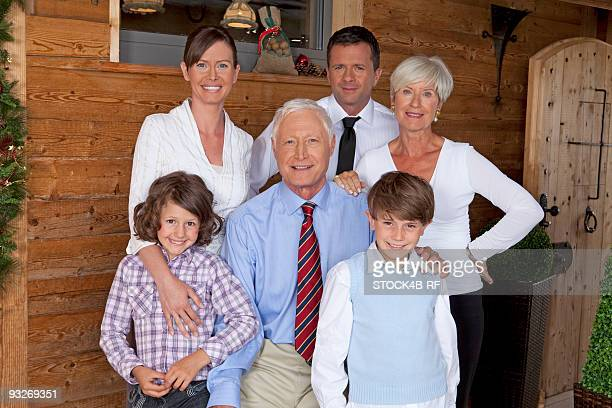 Grandparents, parents and children in front of wooden house