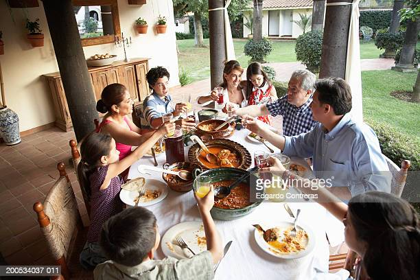 Grandparents, parents and children (7-15) toasting at dinner