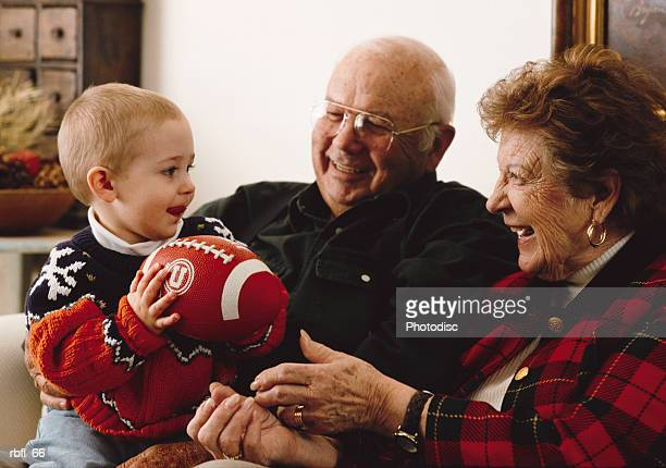 grandparents play with their grandson who holds a stuffed football