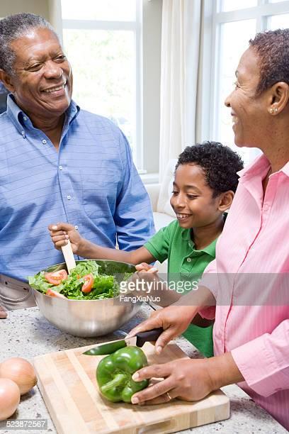 Abuelos y nieto preparar una ensalada