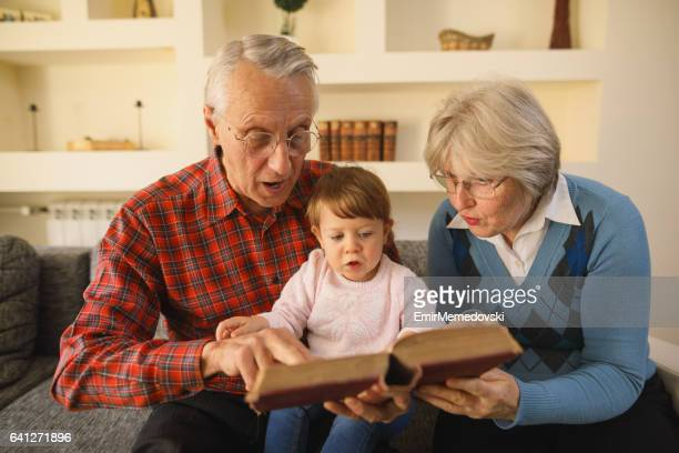 Grandparents reading a book to their granddaughter