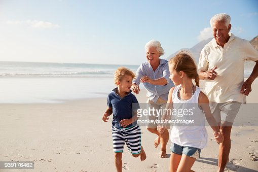 Grandparents Running Along Beach With Grandchildren On Summer Vacation : Stock Photo