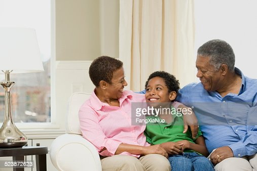 Grandparents Sitting With Grandson on Couch