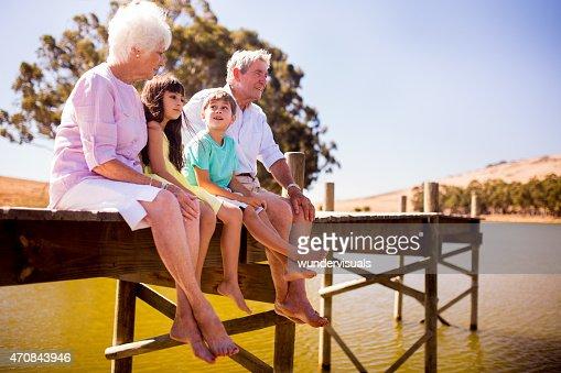 Nonni seduti con i loro nipoti su un pontile