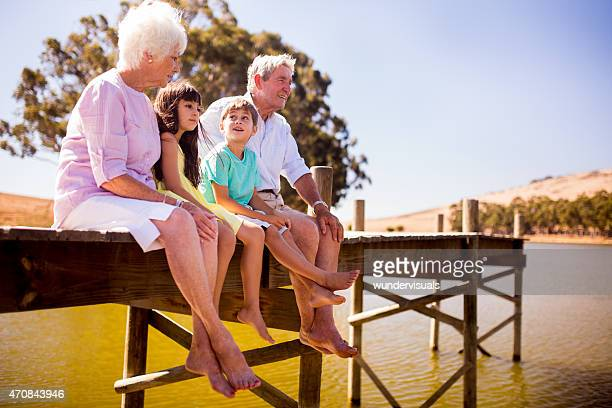 Grandparents sitting with their grandchildren on a jetty