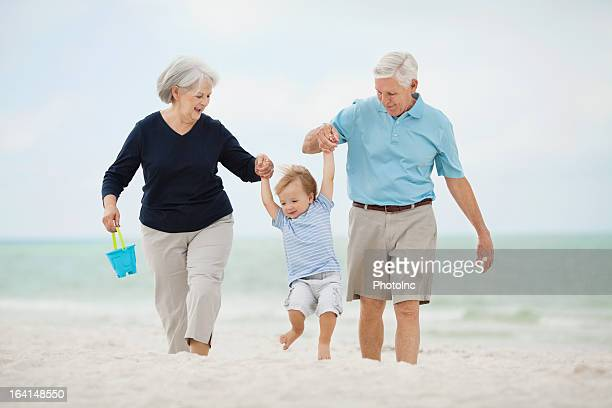 Grandparents Swinging Little Boy At Beach