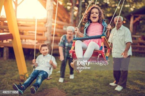 Grandparents swinging their grandchildren.