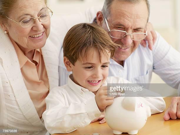 Grands-parents et petit-fils d'enseignement à économiser de l'argent dans une tirelire en forme de cochon