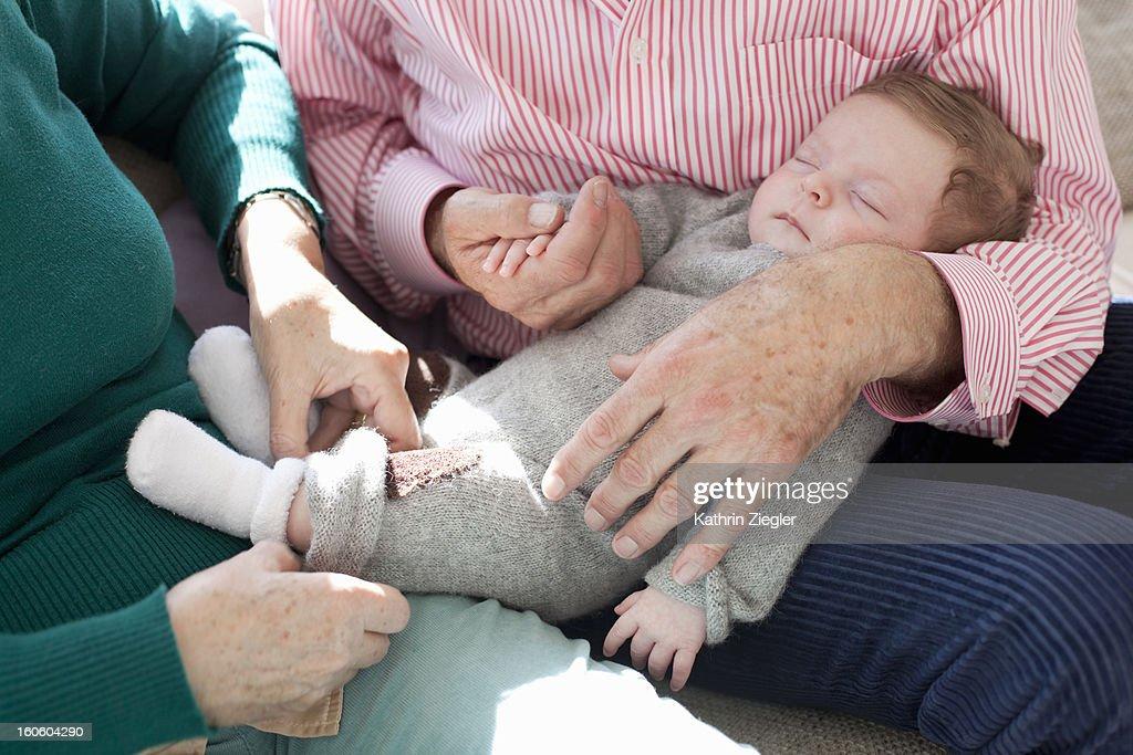 grandparents tenderly holding newborn grandson : Stock Photo