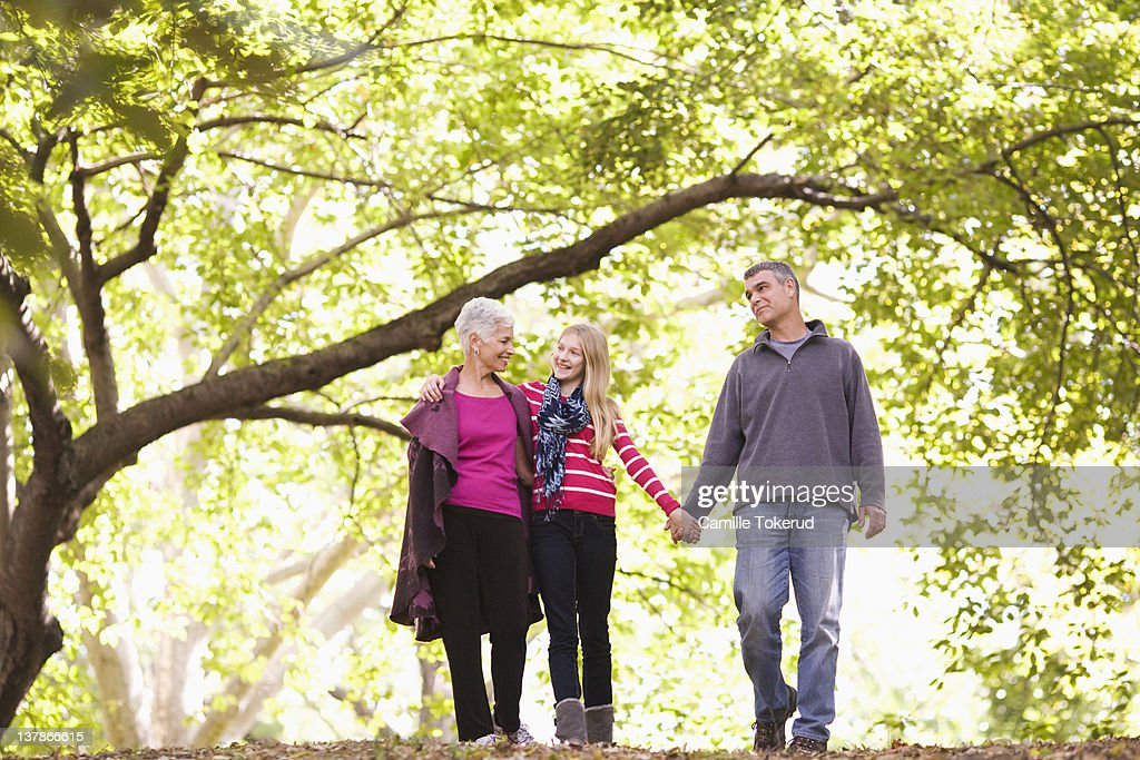 Grandparents walking with granddaughter in park : Stock Photo