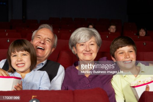 Grandparents Watching Film In Cinema With Grandchildren : Stock-Foto