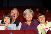 Grandparents Watching Film In Cinema With Grandchildren