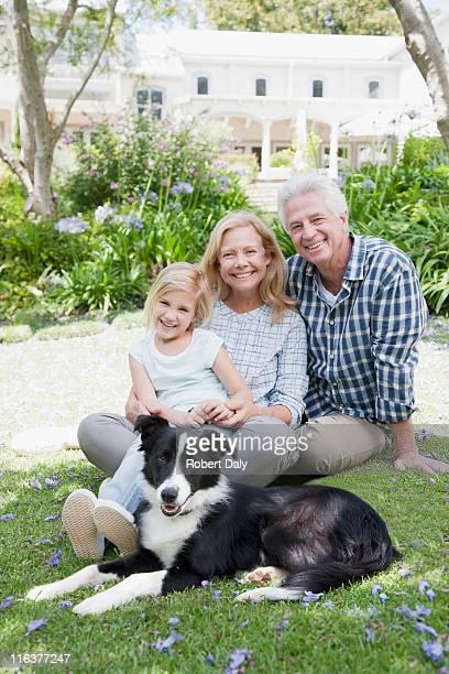 祖父母と孫娘と公園の中の犬
