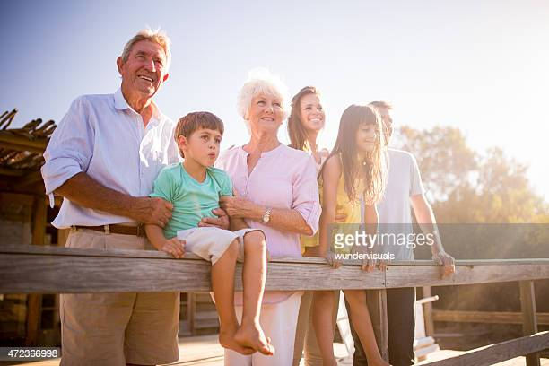 Grandparents with their family outdoors with sun flare