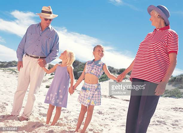 grandparents with their granddaughters standing on a beach