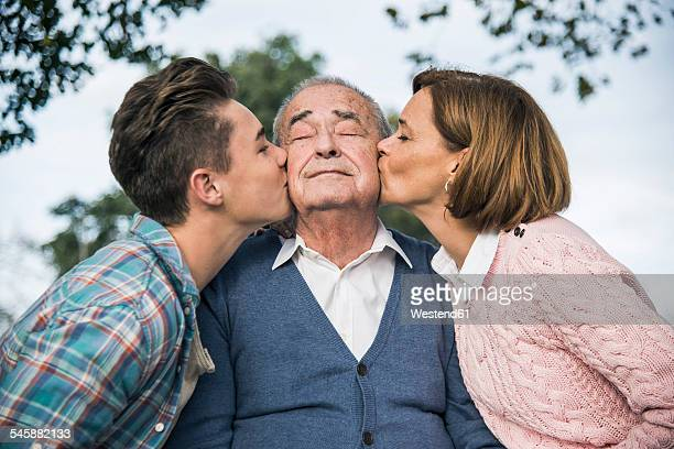 Grandson and daughter kissing senior mans cheek