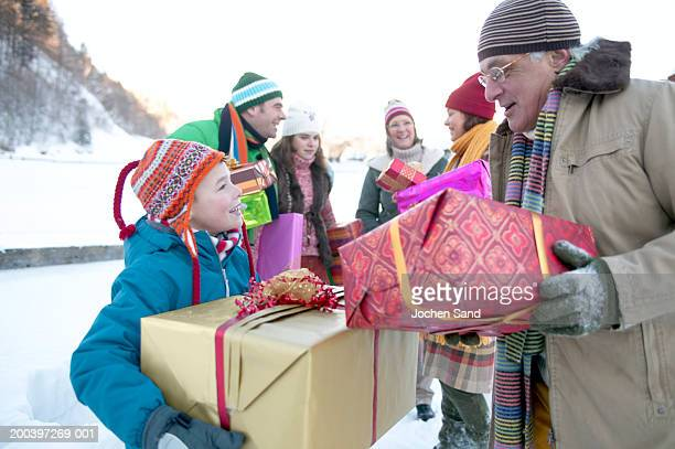 Grandson (8-10) and grandfather carrying presents in snow with family