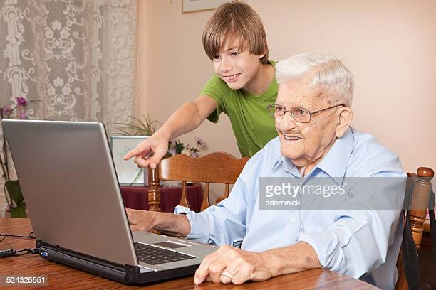 Grandson And Grandfather Enjoying Computer Time Together