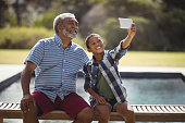 Grandson and grandfather taking selfie with mobile phone near poolside