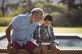 Grandson and grandfather using mobile phone near poolside