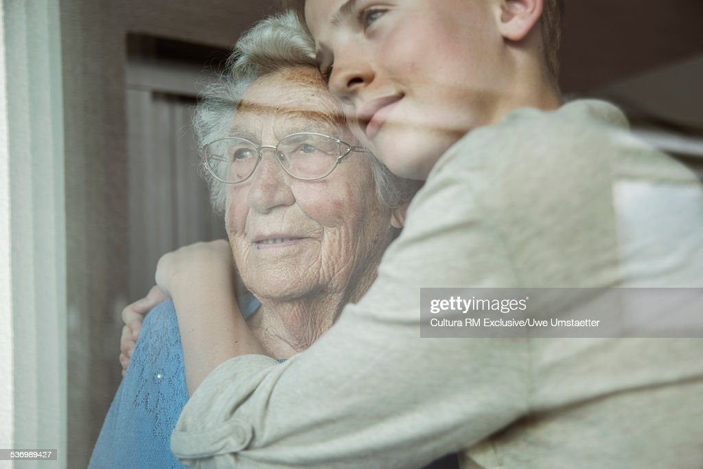 Grandson and grandmother looking out of glass window