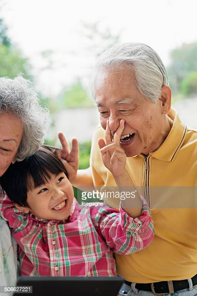 Grandson and grandparents taking selfie with digital tablet