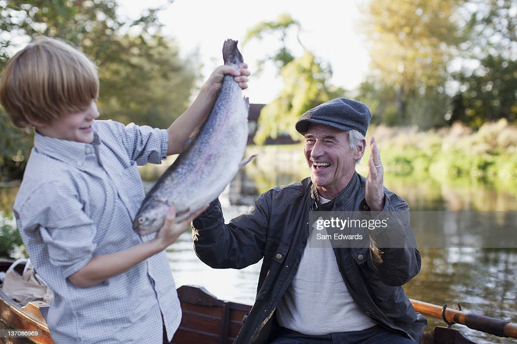Grandson catching fish with grandfather cheering in background : Stock Photo