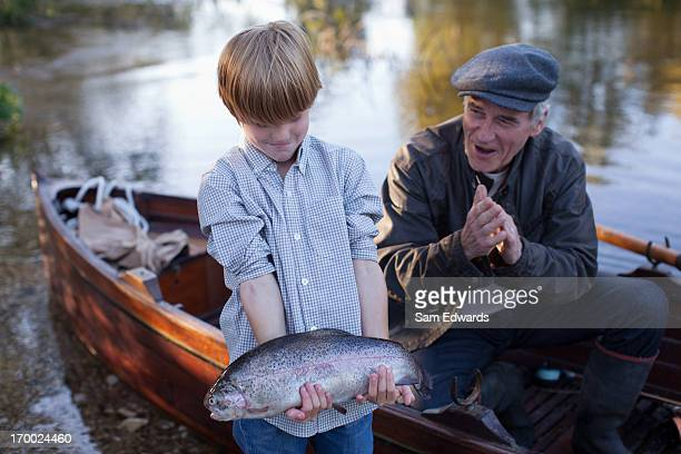 Grandson catching fish with grandfather cheering in background