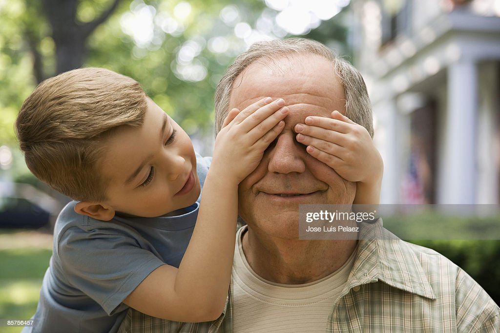 Grandson covering grandfather's eyes : Stock Photo