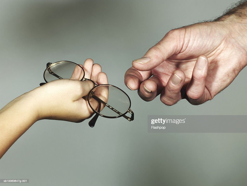 Grandson (6-7) giving spectacles to grandfather, close-up : Stock Photo