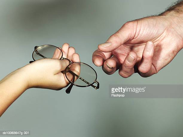 Grandson (6-7) giving spectacles to grandfather, close-up