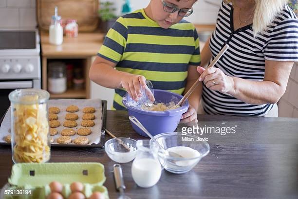 Grandson Helping Grandmother To Bake coockies In Kitchen