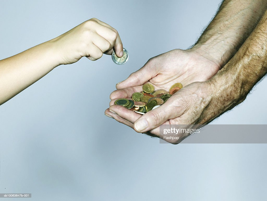 Grandson (4-5) placing coin into grandfather's hand, close-up : Stock Photo