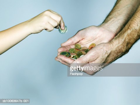 Grandson (4-5) placing coin into grandfather's hand, close-up : Foto stock