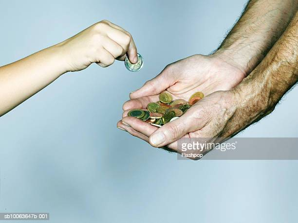 Grandson (4-5) placing coin into grandfather's hand, close-up