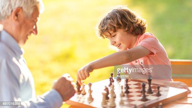 Grandson playing chess with his grandfather