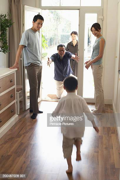 Grandson (4-5) running to greet grandfather at doorway