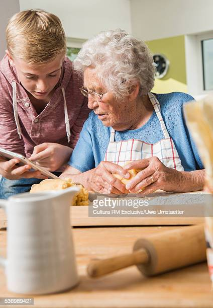 Grandson showing digital tablet to grandmother kneading dough