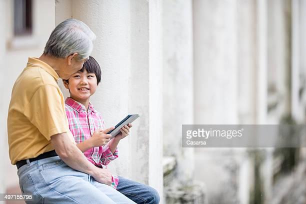 Grandson showing grandfather his Digital tablet